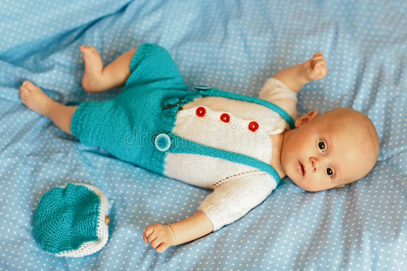 Portrait of a three months old baby boy on the bed on a blue blanket in nursery room. Flat lay royalty free stock images