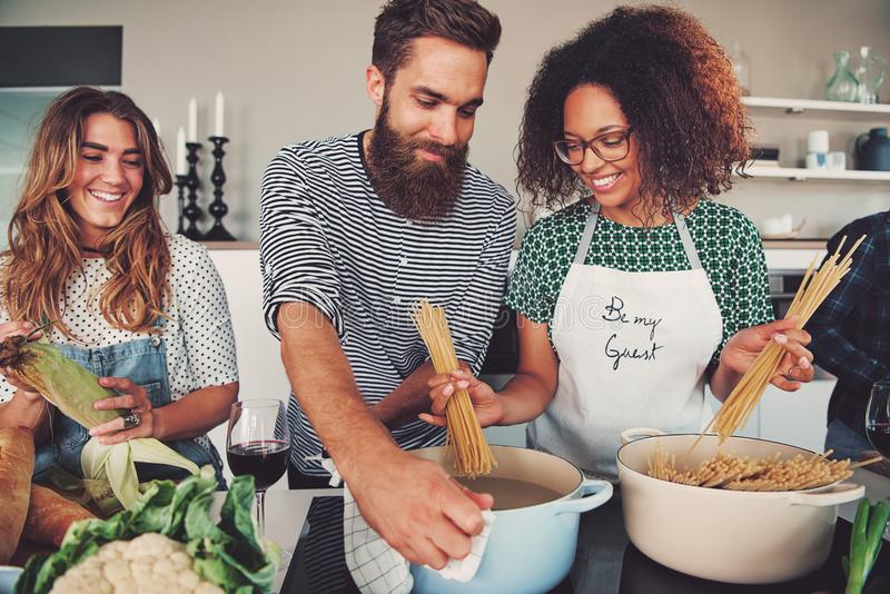 Three friends cooking spaghetti stock photos