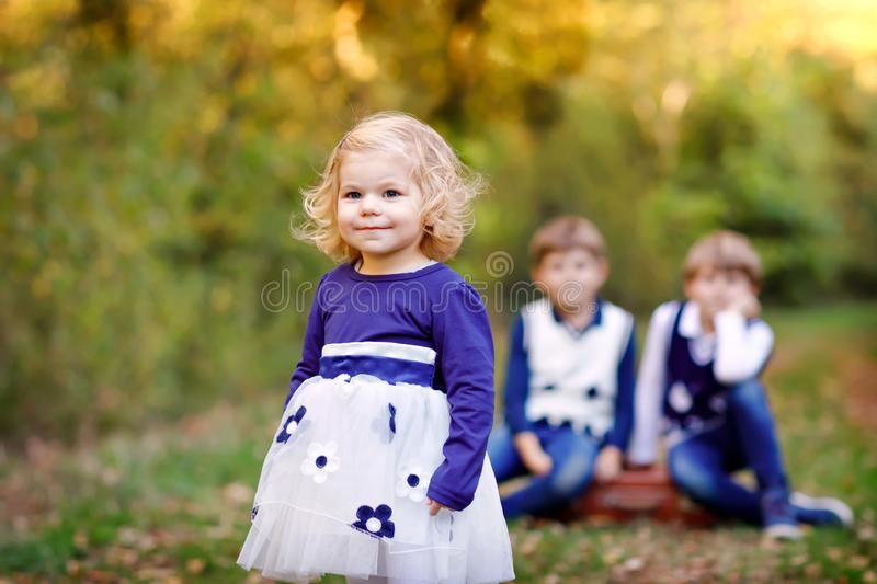 Portrait of three siblings children. Little cute toddler sister girl and Two kids brothers boys on background having fun royalty free stock photo