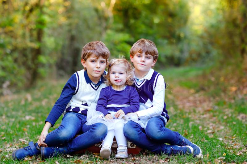 Portrait of three siblings children. Two kids brothers boys and little cute toddler sister girl having fun together in stock photography