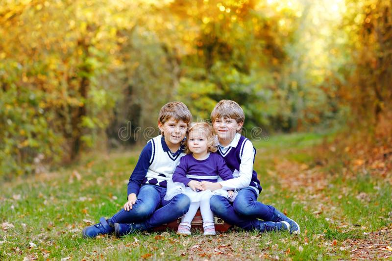 Portrait of three siblings children. Two kids brothers boys and little cute toddler sister girl having fun together in royalty free stock photography