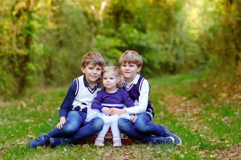 Portrait of three siblings children. Two kids brothers boys and little cute toddler sister girl having fun together in royalty free stock images