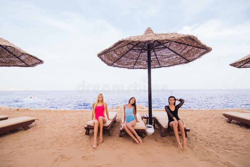 Portrait of three women friends sitting and resting in lounge chairs with umbrella on the sea beach. Summer vocation. royalty free stock images