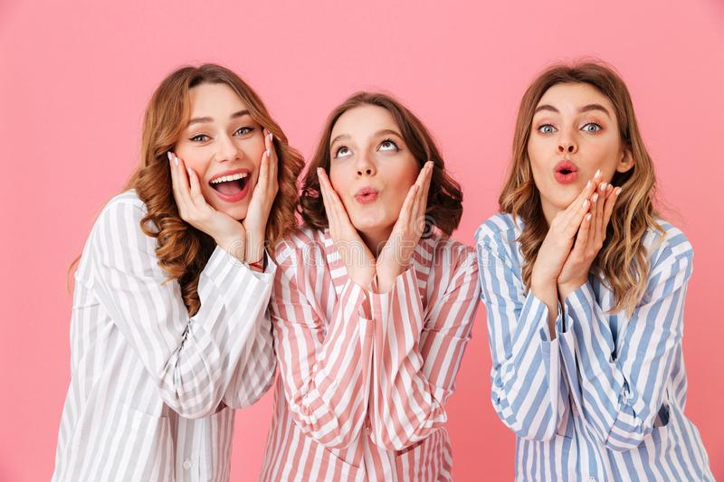 Portrait of three women friends wearing leisure clothing touching cheeks and smiling while enjoying girlish party during. Sleepover isolated over pink stock images