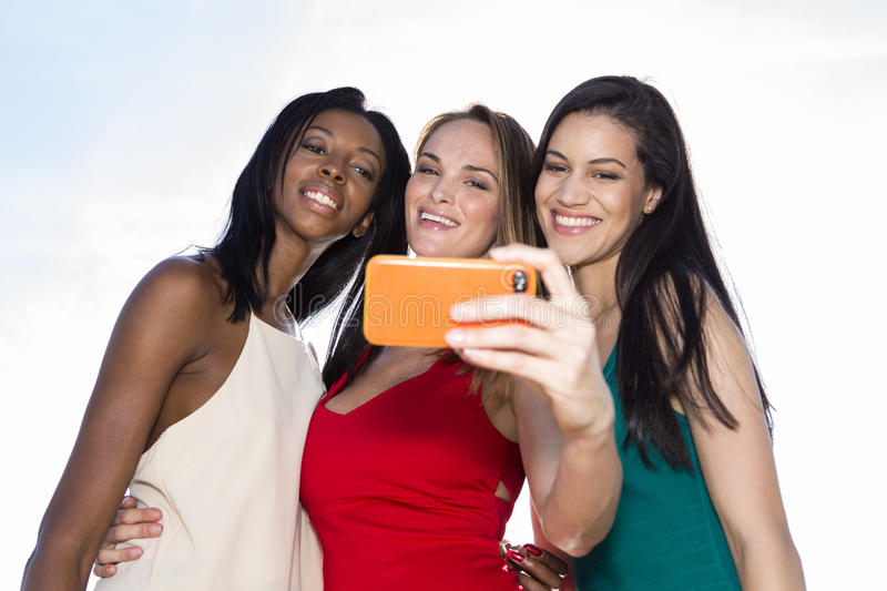 Portrait of three women taking selfies with a smartphone. stock images