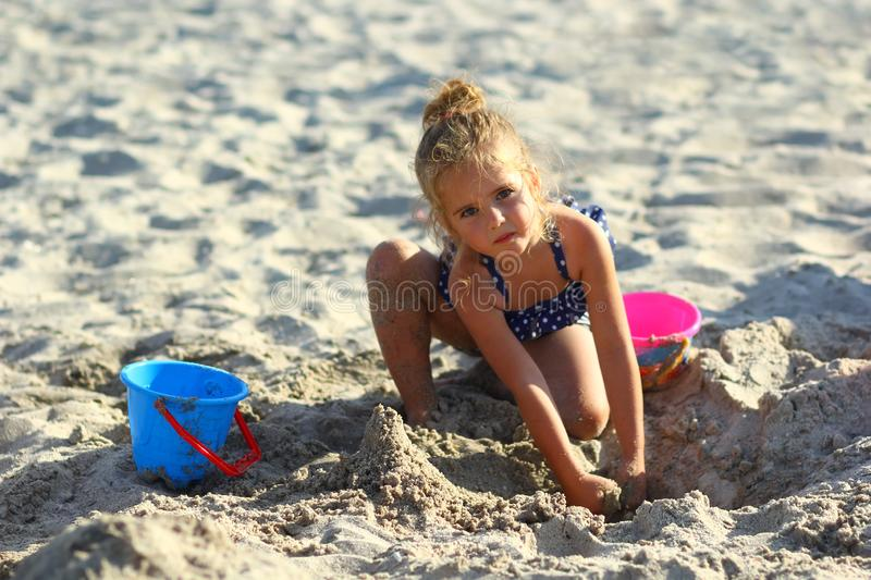 Portrait of a three year old caucasian girl playing with sand on the beach royalty free stock image
