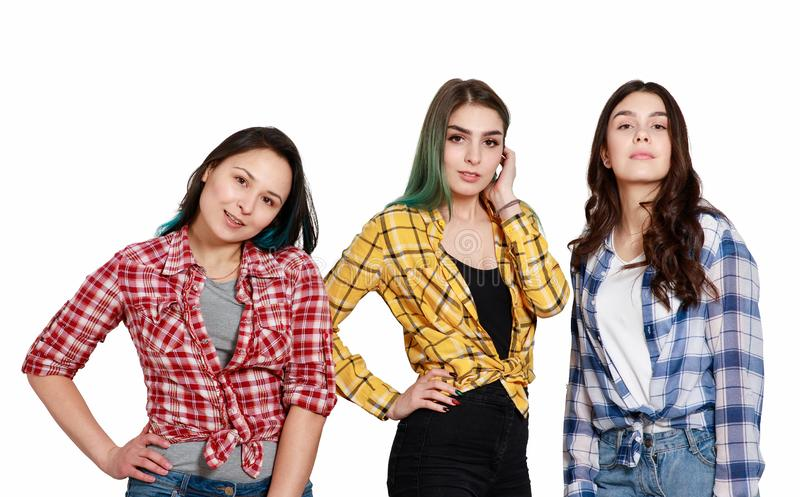 Portrait of three young beautiful slender girls women in plaid shirts red, yellow and blue. isolated on white stock photos