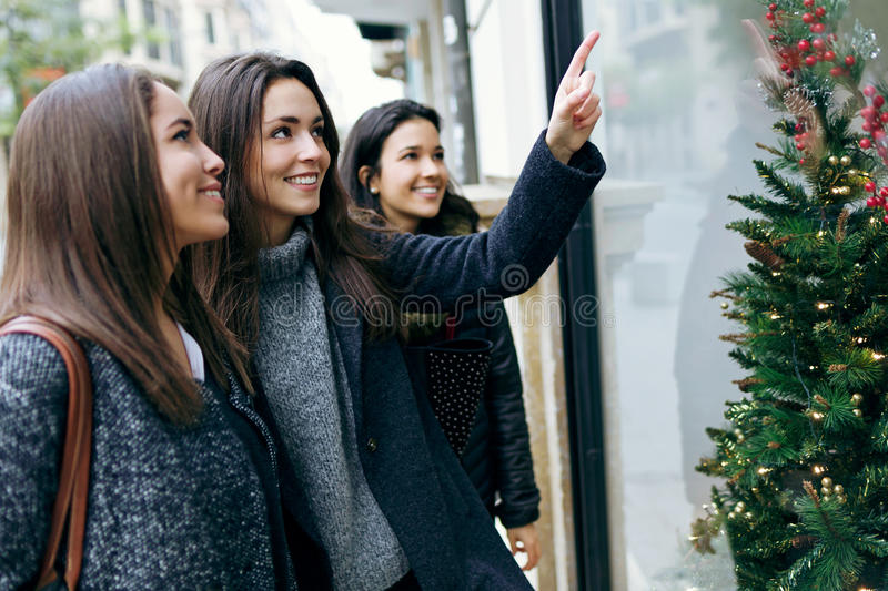 Portrait of three young beautiful women looking at the shop wind royalty free stock images