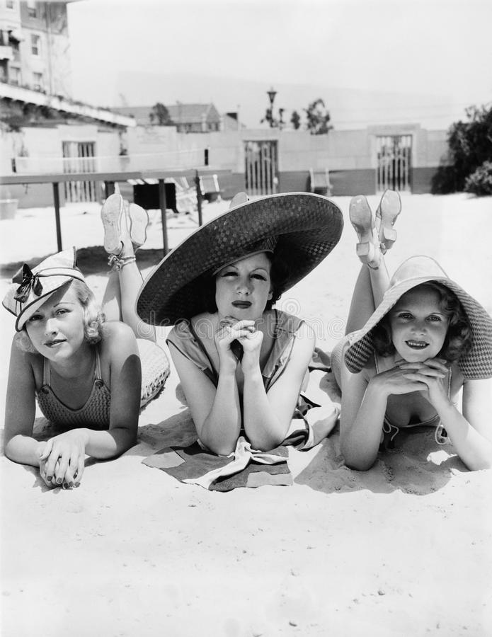 Portrait of three young women lying on the beach stock images