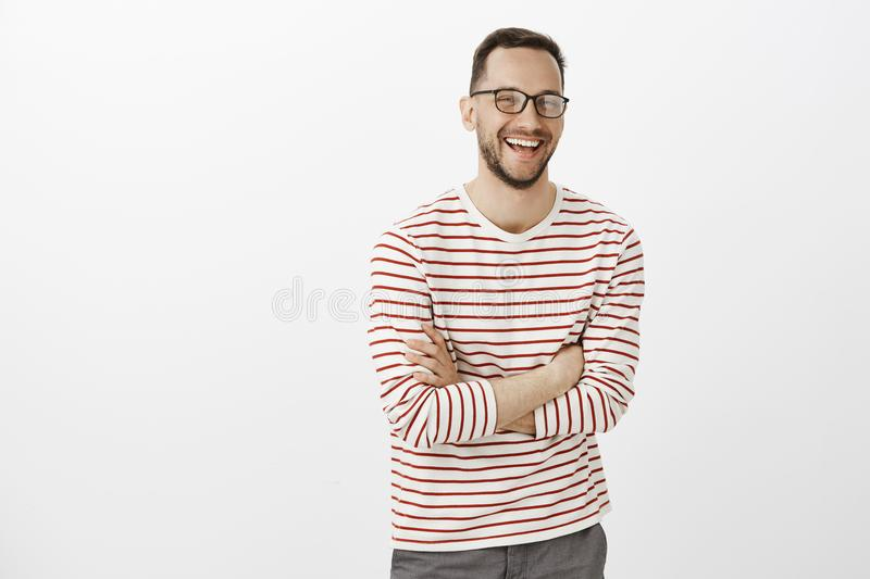 Portrait of timid good-looking european male with beard in glasses, crossing hands over chest and laughing out loud royalty free stock photo