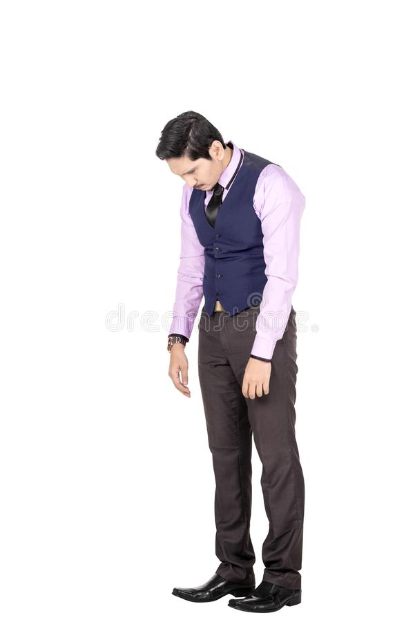 Portrait of tired asian businessman with head down. Posing isolated over white background stock photography