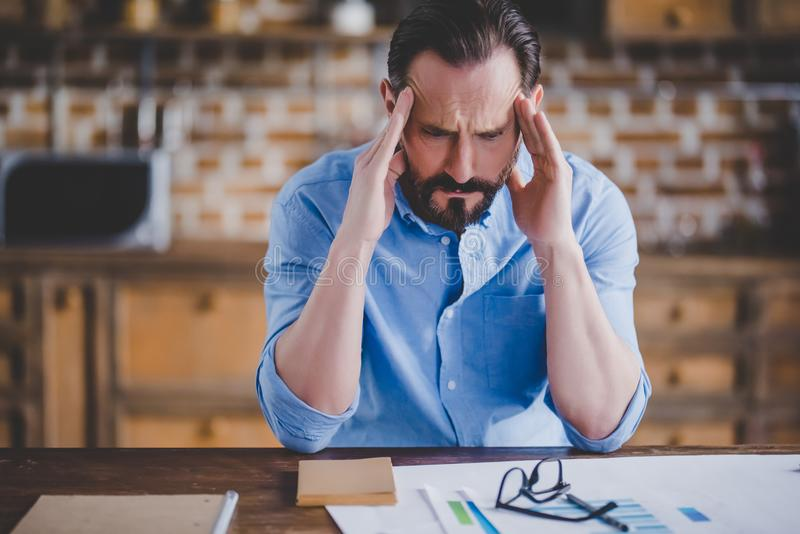 Tired businessman with migraine after work. Portrait of tired businessman with migraine after work at home office royalty free stock photo