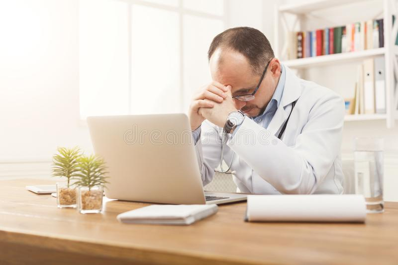 Portrait of tired doctor in glasses sitting at the desktop royalty free stock image