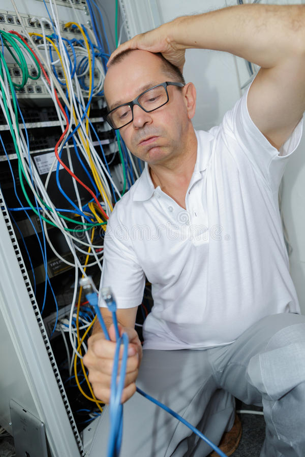 Portrait tired electrician scratching head stock photo