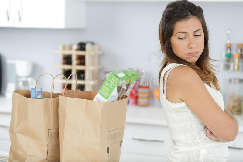 Portrait tired girl holding bag with groceries. Portrait of a tired girl holding bag with groceries royalty free stock photography