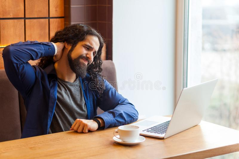 Portrait of tired handsome young adult man freelancer in casual style sitting in cafe with laptop, holding his neck after hard. Overtime work and make massage stock photos