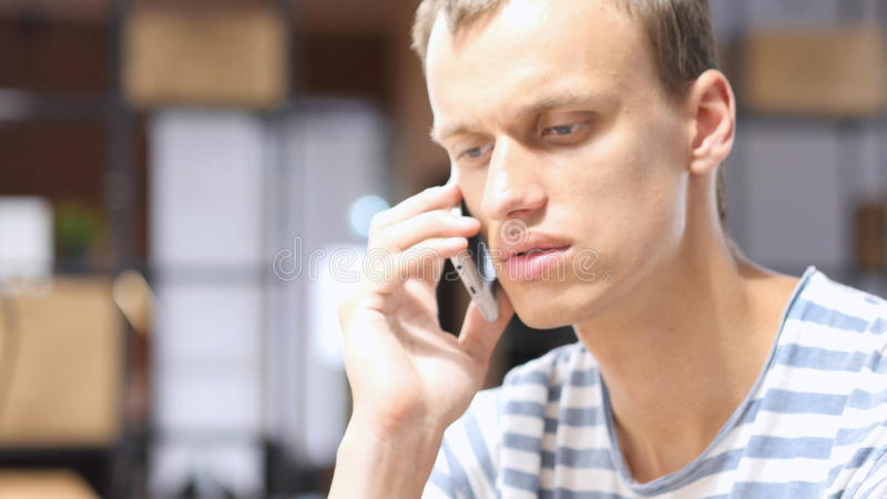 Portrait of Tired man talking on the phone, Discussing issue on phone royalty free stock images