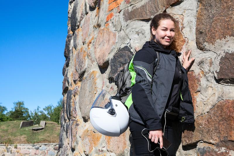 Portrait of tired motorcyclist woman resting near stone wall after tramp a fortress in apparel, with backpack and helmet attached stock image