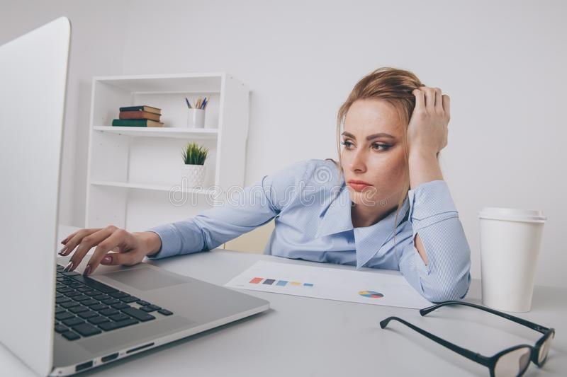 Portrait of tired office woman working by computer. Laptop problem. royalty free stock image