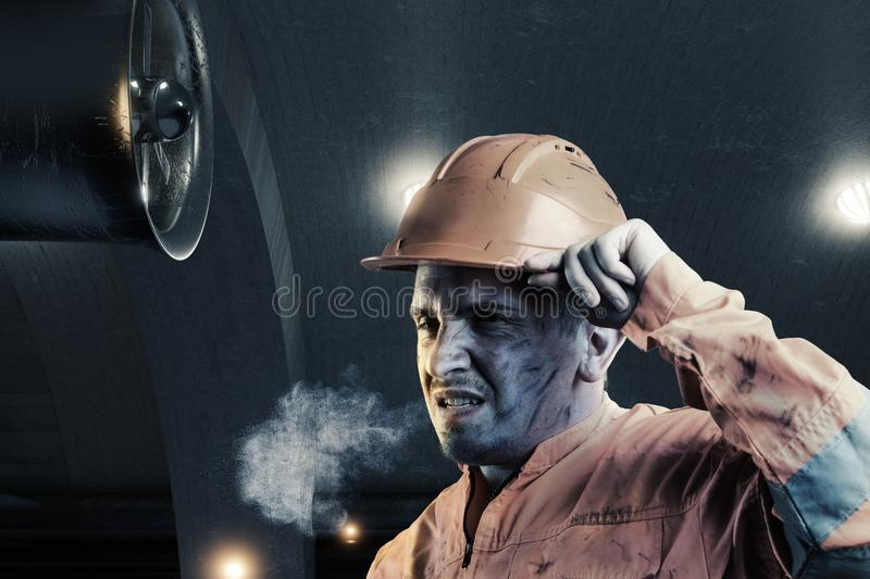 portrait of tired rail worker with orange unifom and helmet light in front of tunnel at night royalty free stock photography