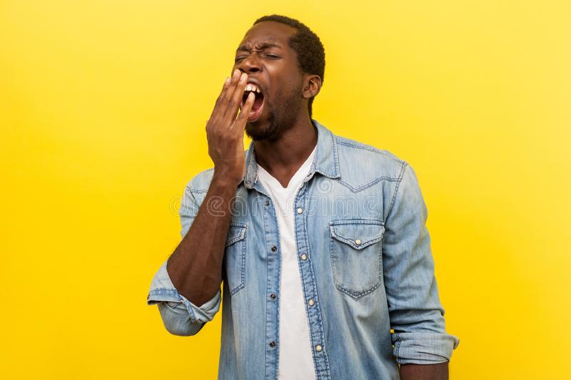 Portrait of tired worker, exhausted man yawning covering mouth with hand. indoor studio shot isolated on yellow background royalty free stock photos