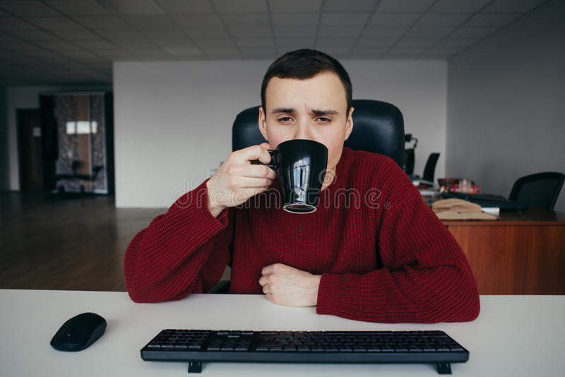 Portrait of a tired young office worker drinking coffee at work. The situation in the office royalty free stock image