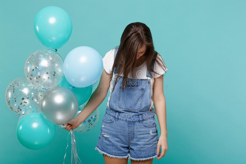 Portrait of tired young woman in denim clothes with lowered head celebrating, holding colorful air balloons isolated on. Blue turquoise wall background stock photography