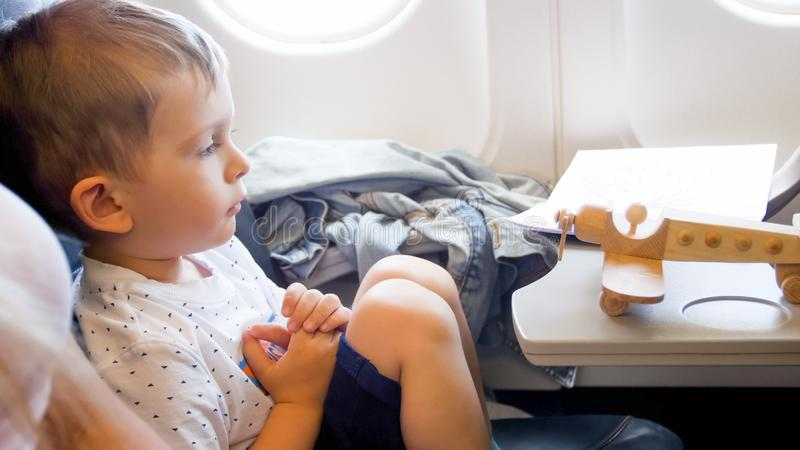 Portrait of little toddler boy looking on wooden toy airplane during flying in plane stock photography