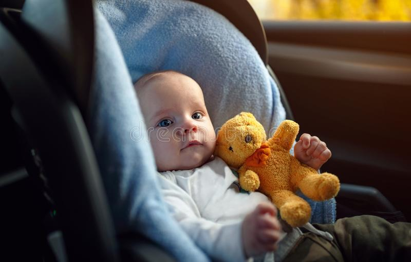 Portrait of toddler boy sitting in car seat. Child transportation safety royalty free stock image