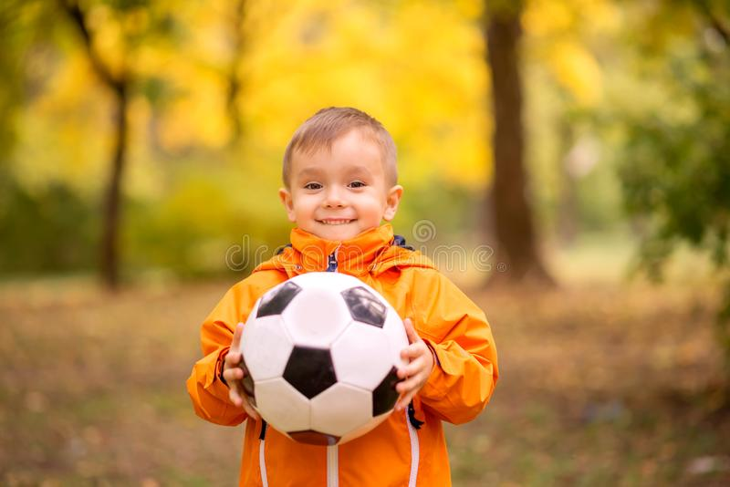 Portrait of toddler boy with soccer ball in autumn park. Healthy childhood, sports and outdoor activities concept royalty free stock photos