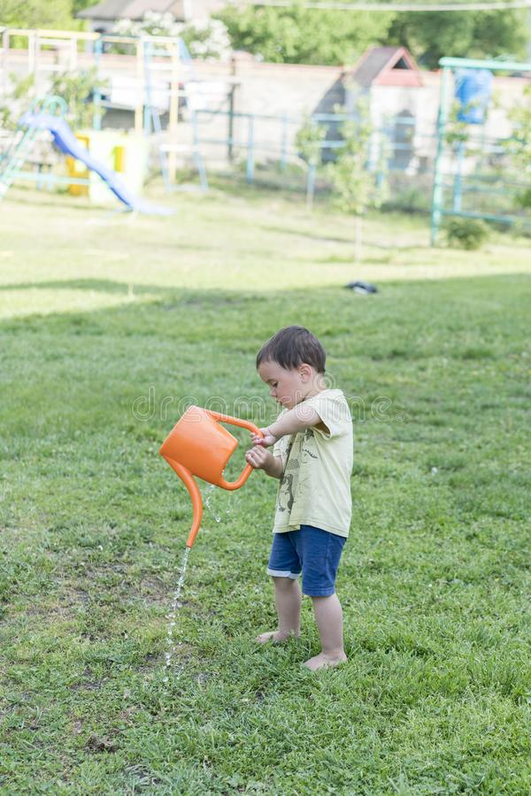 Portrait of toddler child outdoors. Rural scene with one year old baby boy wearing straw hat using watering can. Boy watering tree stock photos