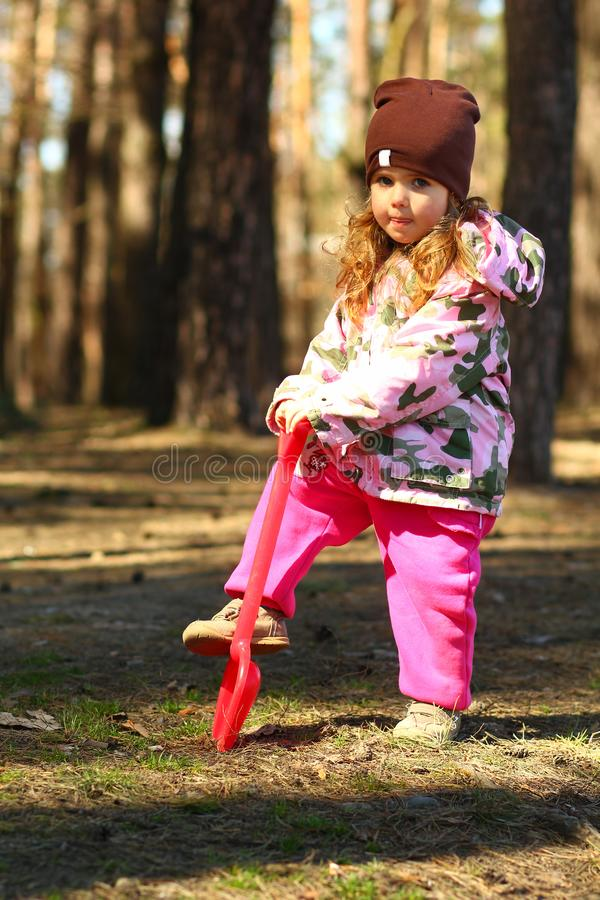 Portrait of a toddler girl digging the forest ground with a toy red shovel stock photography
