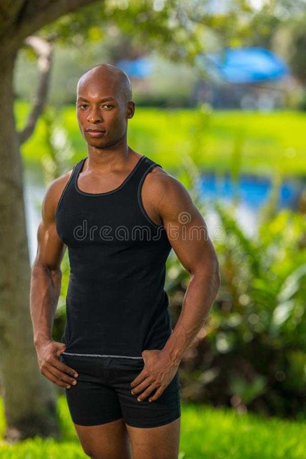 Portrait of a tough guy in a tank top shirt posing outdoors royalty free stock photo