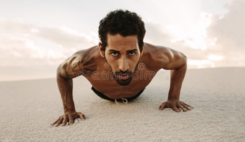 Male athlete doing push ups on desert sand. Portrait of tough young male athlete doing push ups on desert sand. Fit man working out in sand dune in evening stock photography