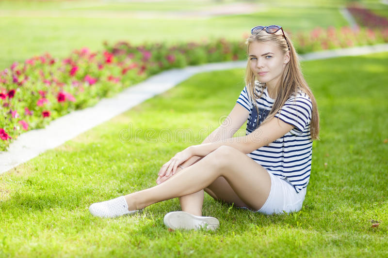 Portrait of Tranquil Caucasian Blond Teenage Girl Posing on the Grass in Green Flowery Summer Park stock images