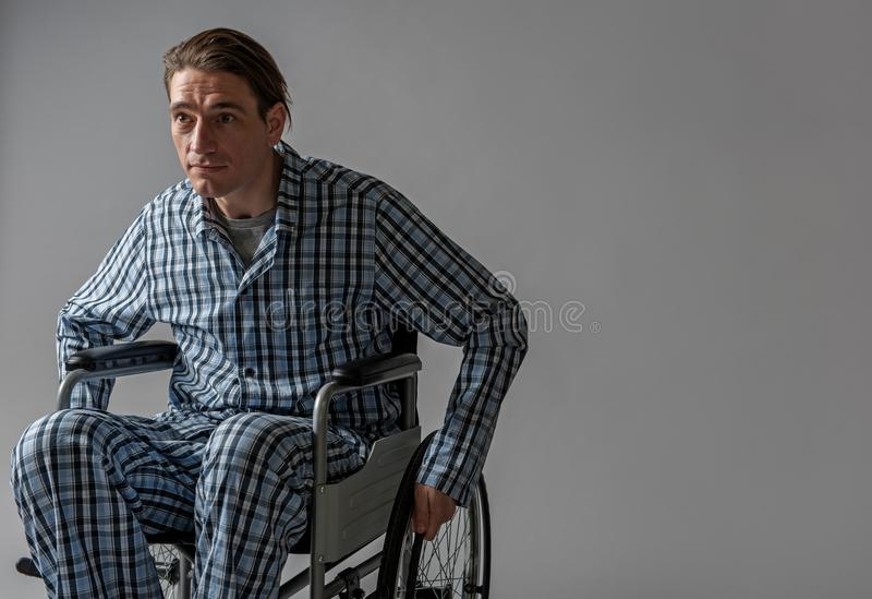 Calm male invalid moving in wheelchair royalty free stock photo