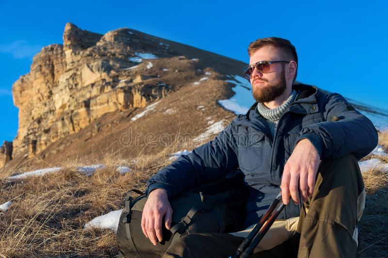 Portrait of tranquil Hipster traveler with beard in sunglasses is sitting on nature. stock images