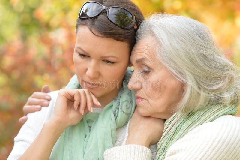 Portrait trauriger älterer Frau mit erwachsener Tochter im Herbstpark stockbild