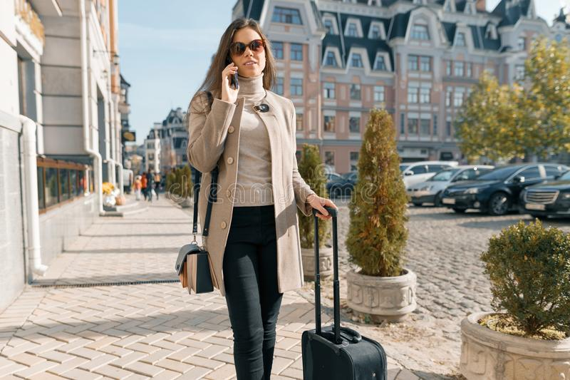 Portrait of traveling young woman with mobile phone and suitcase, fashionable girl on the city street, wearing warm coat, sunny royalty free stock photo