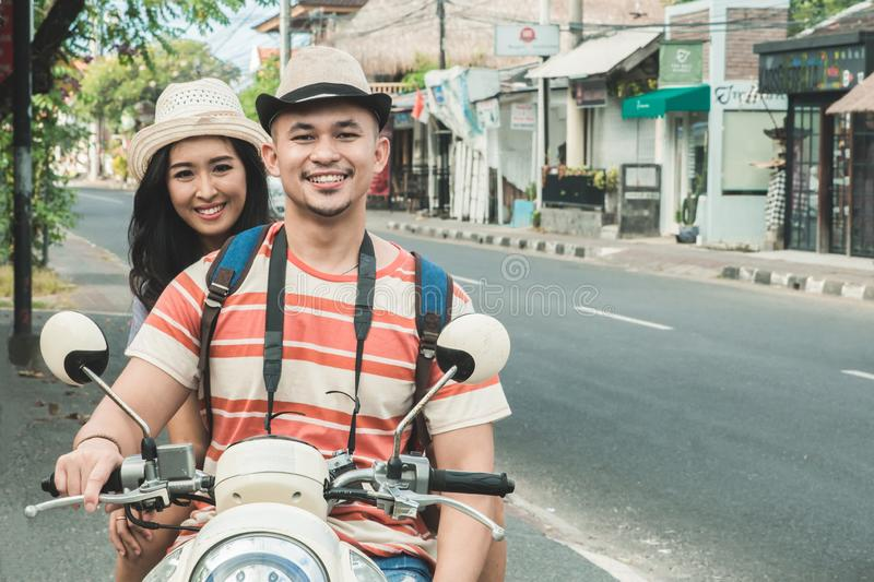 Travellers couple smiling on camera while sitting on motorbike. Portrait of travellers couple smiling on camera while sitting on motorbike on the side of the stock photo