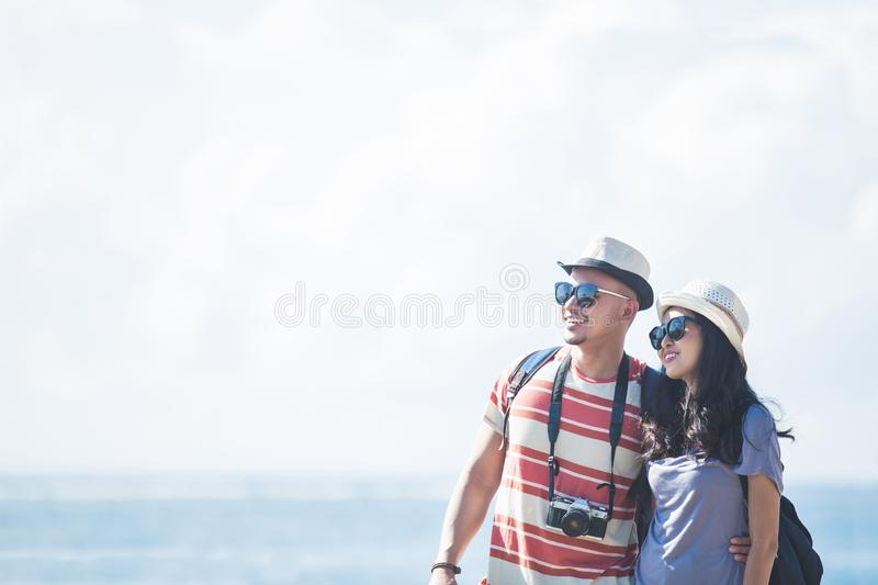Travellers couple wearing summer hat and sunglasses during vacat. Portrait of travellers couple wearing summer hat and sunglasses during vacation on sunny day stock photos