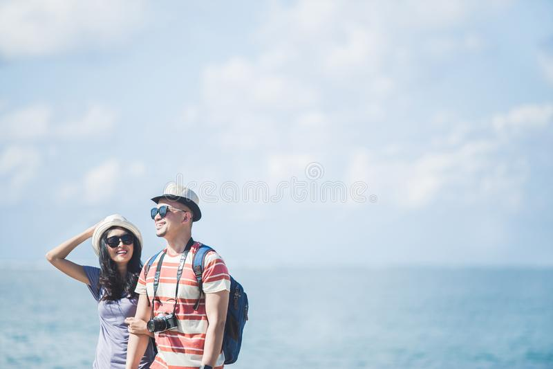 Travellers couple wearing summer hat and sunglasses during vacat. Portrait of travellers couple wearing summer hat and sunglasses during vacation on sunny day royalty free stock photo
