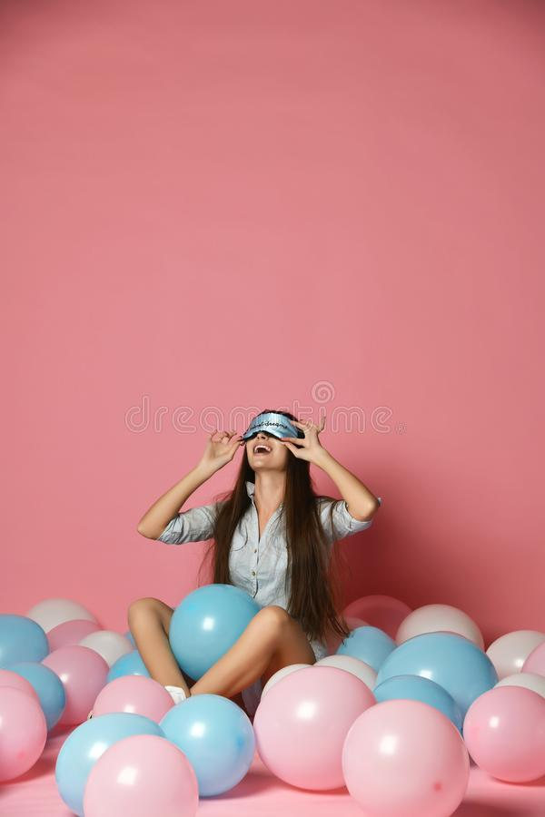 Portrait of trendy cheerful young woman having many color air balloons looking up enjoying ballons isolated on pink background. royalty free stock photos