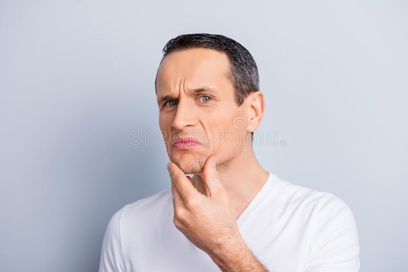 Portrait of trendy, experienced, neat, brunet, expertising, exam. Ine his face, looking at camera holding hand on chin with dislike expression, on grey stock photography