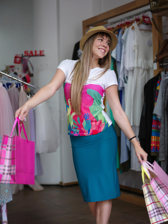 A portrait of a trendy woman with shopping bags in her hands in a clothing store. Shopping concept. Copy space. An attractive and happy woman holding colorful stock images