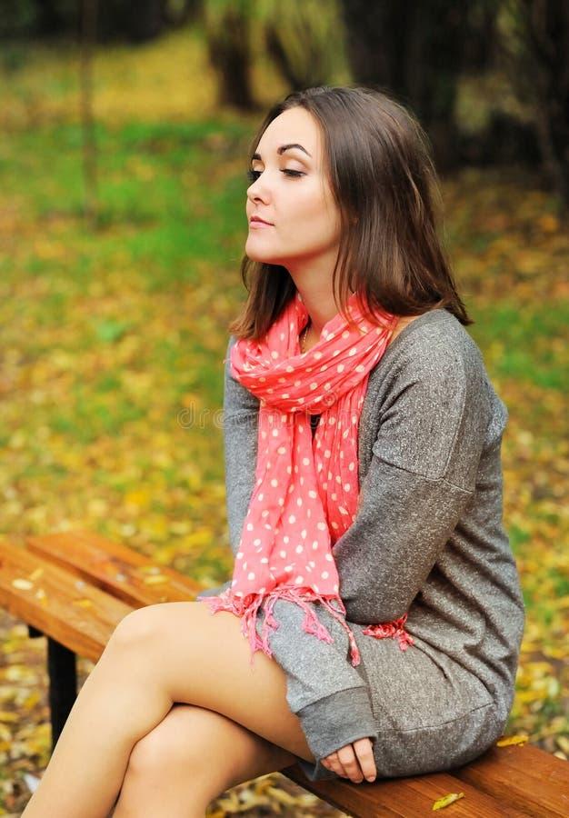 Portrait triste de femme se reposant sur un banc photo stock