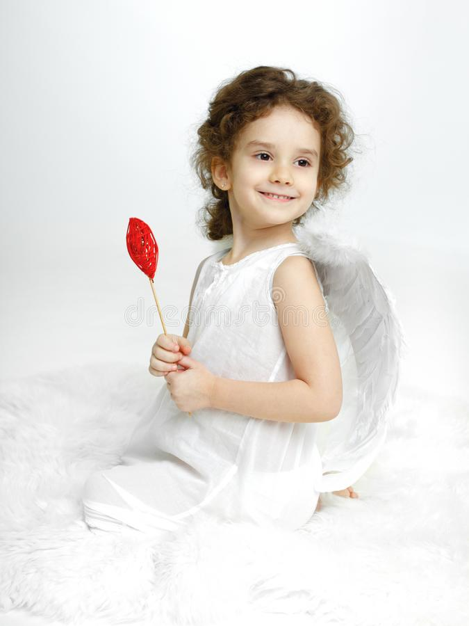 Portrait of turned little girl with angelic smiling in white dress and wings, holding red heart, over white background. stock image