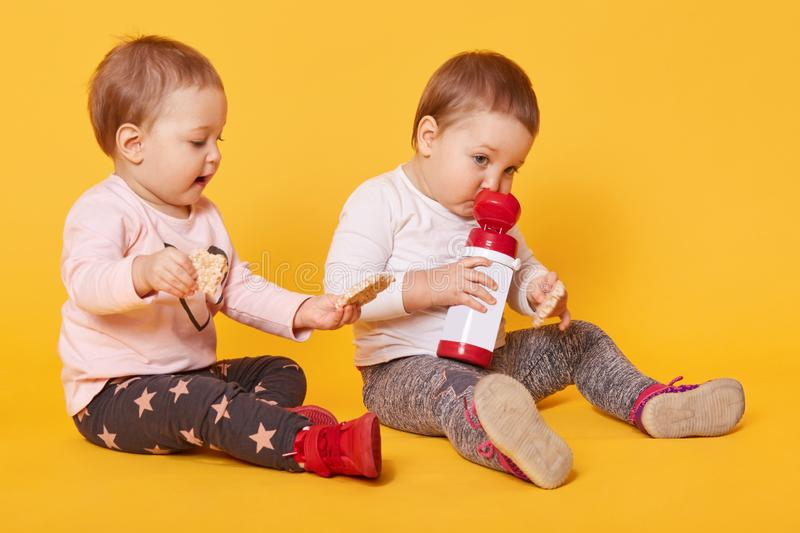A portrait of two adorable beautiful children share delicious food together, make friends, enjoy moments of their childhood. Having rest after a tiresome stock image