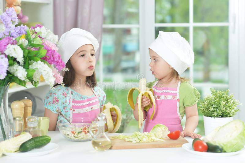 Portrait of two adorable little girls in aprons eating bananas at kitchen stock image