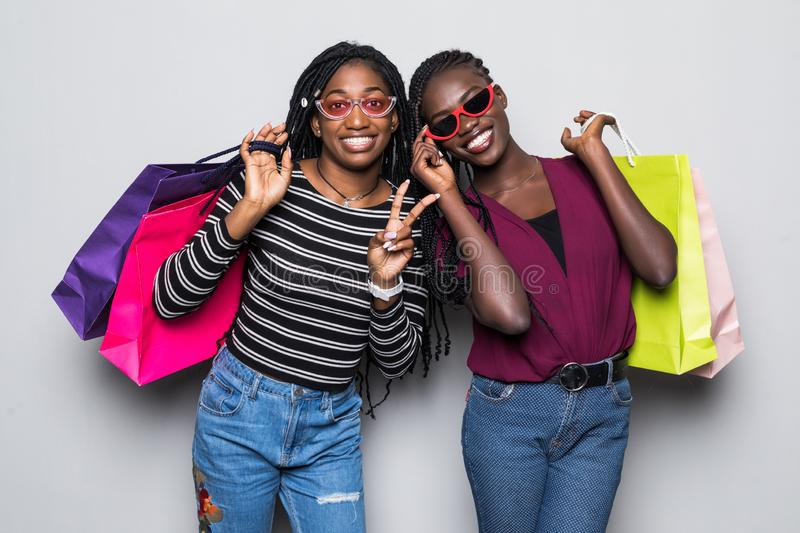 Portrait of two african young girls holding shopping bags isolated over white background royalty free stock photos